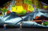 Dos figuras sostienen un globo terrestre desinflado.
