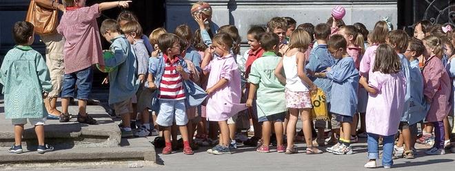 Niños y niñas de Infantil formando en fila a la entrada de un colegio.