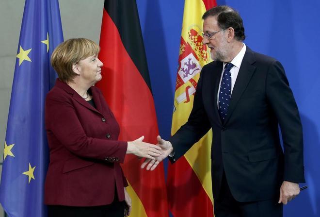 Angela Merkel y Mariano Rajoy se saludan tras participar en la cumbre...