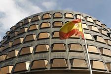 La bandera de España ondea junto a la fachada del edificio sede del...