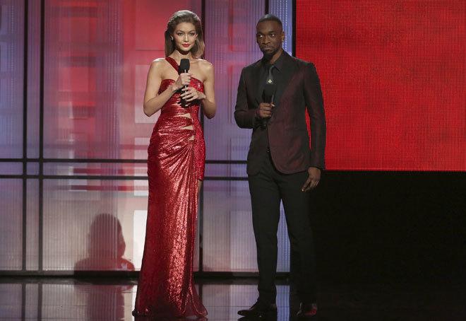 Gigi Hadid, con vestido rojo de Atelier Versace, junto a Jay Pharoah.