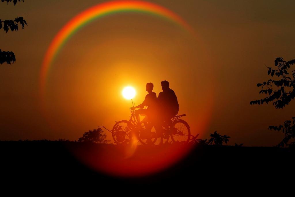 Siluetas de ciclistas al atardecer en las cercanías de Agartala, la...