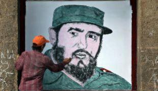 Un hombre pinta la imagen de Fidel Castro en una fachada de La Habana