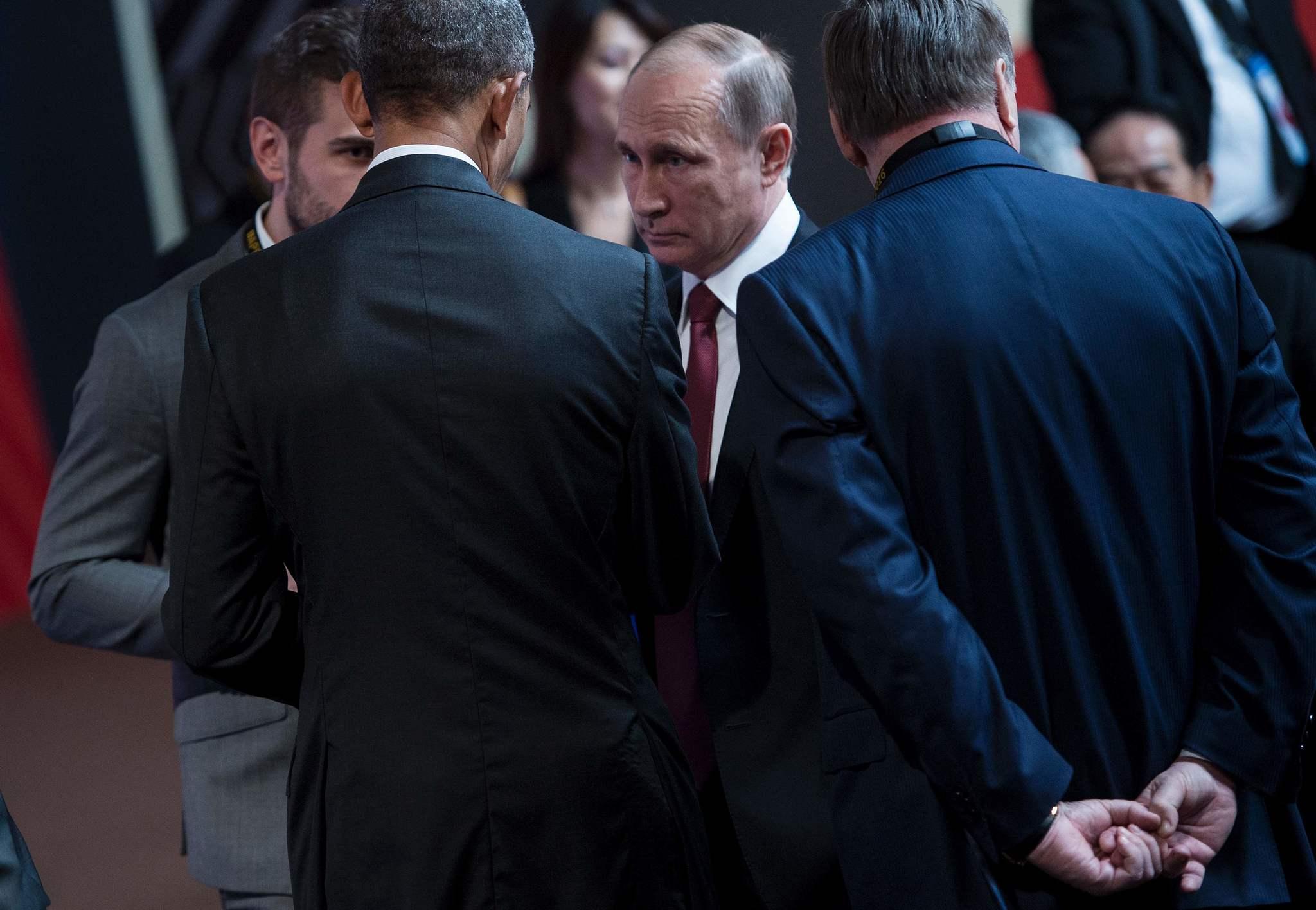 El presidente ruso, Vladimir Putin, junto a su homólogo de EEUU, Barack Obama, de espaldas.