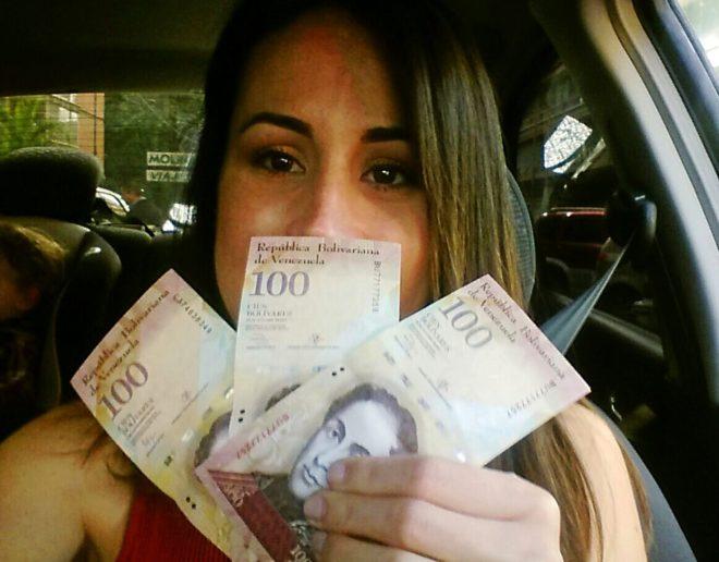Una venezolana muestra sus tres últimos billetes de cien bolívares