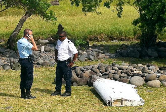 Dos agentes de policía, junto a restos hallados del vuelo MH370.