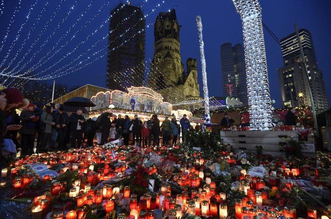 Velas y las flores colocadas tras la reapertura del mercado navideño de Breitscheidplatz en Berlín.