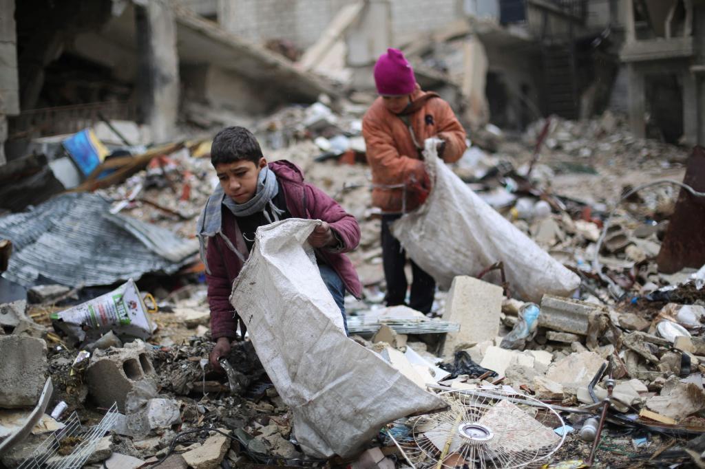Jóvenes sirios recogen madera entre los escombros que utilizarán...