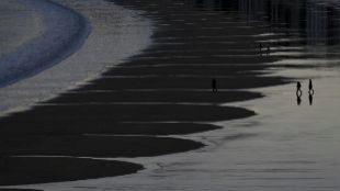 Varias personas pasean, ayer, por la orilla de la playa de La Concha,...