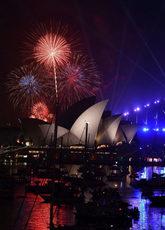 Los fuegos artificiales iluminan el cielo nocturno sobre la Opera...