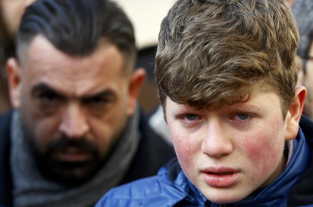 Un niño llora desconsolado durante el funeral de una de las...