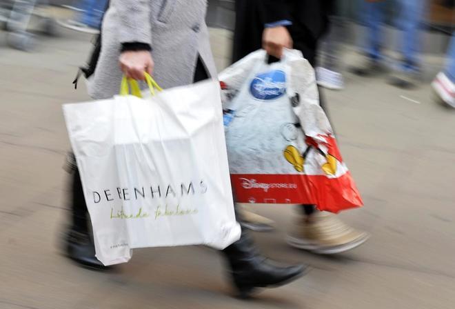 Unas personas realizando compras navideñas en Londres, Reino Unido.