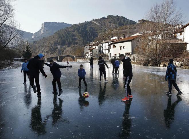 Un grupo de jóvenes juegan al balón sobre la superficie helada del...