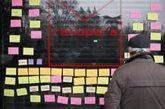 Un hombre lee los mensajes de la fachada de la sede de la asociación,...