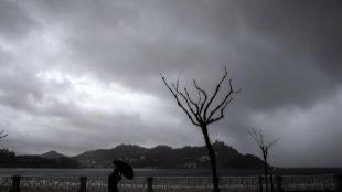 Una persona se protege del viento y la lluvia en San Sebastián.