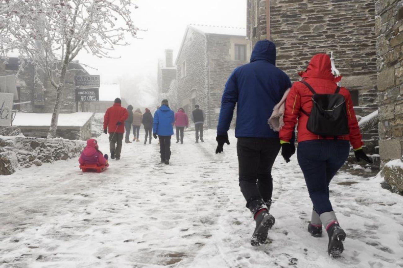 Visitantes caminan en las heladas calles de O Cebreiro, donde el...