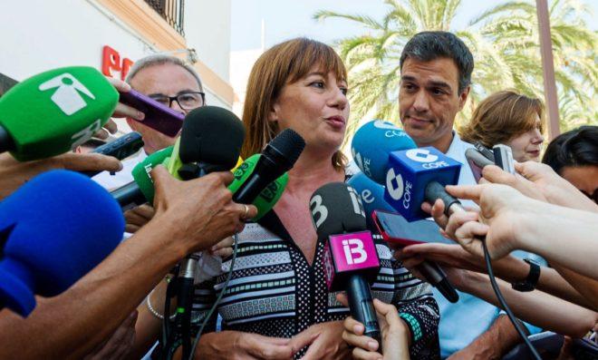 Francina Armengol atendiendo a los medios este verano en Ibiza ante la mirada de Pedro Sánchez.