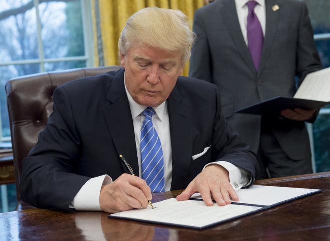 Donald Trump firma el documento que anuncia la salida de EEUU del TPP.