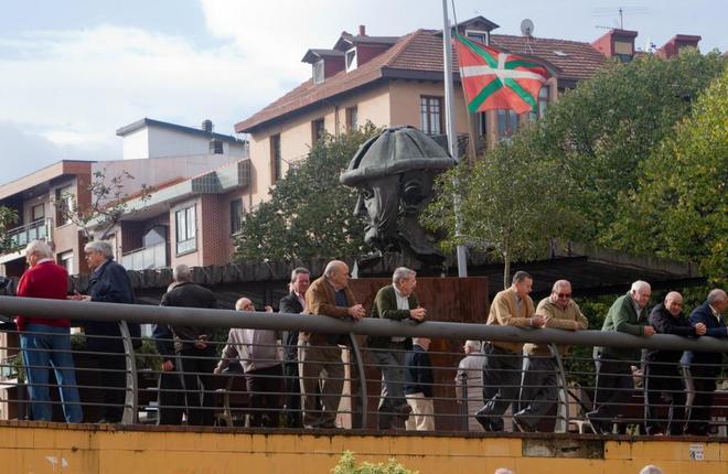 Un grupo de jubilados junto al monumento al obrero, en Sestao.