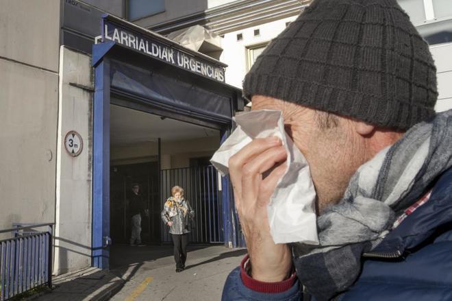 Un afectado por la gripe junto a las urgencias del hospital de Txagorritxu de Vitoria.