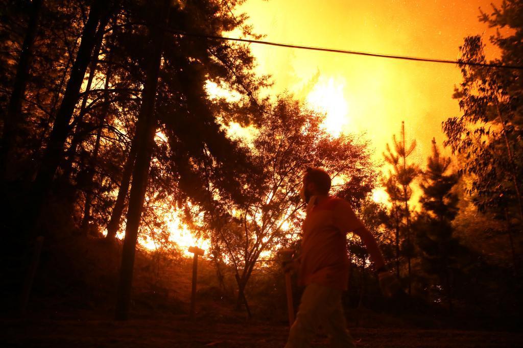 Un hombre huye de un incendio forestal en la localidad de Vichuquen,...