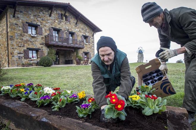 Alberto Agirrebeitia planta flores en el exterior de la casa rural...