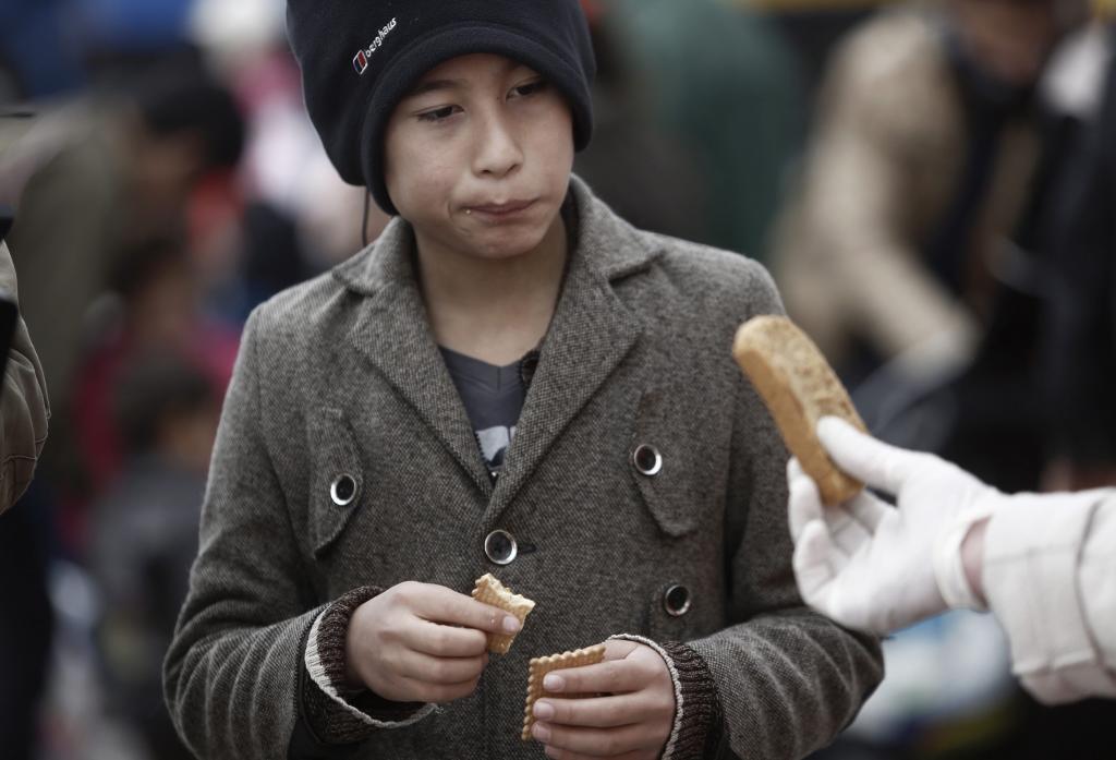 Un niño refugiado recibe unas galletas a su llegada a la isla griega de Lesbos.