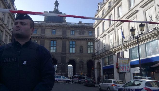 Un policía vigila uno de los accesos a la plaza del Louvre.