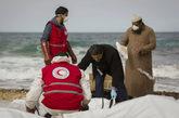 Un grupo de voluntarios atiende a uno de los cuerpos de la playa de...