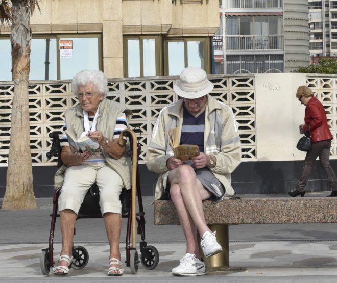 Una pareja de jubilados se entretiene leyendo en un banco del paseo de Benidorm.