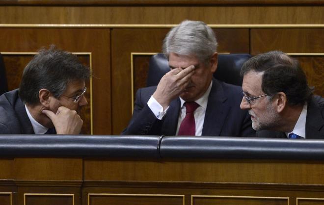 El presidente del Gobierno, Mariano Rajoy, junto al ministro de...