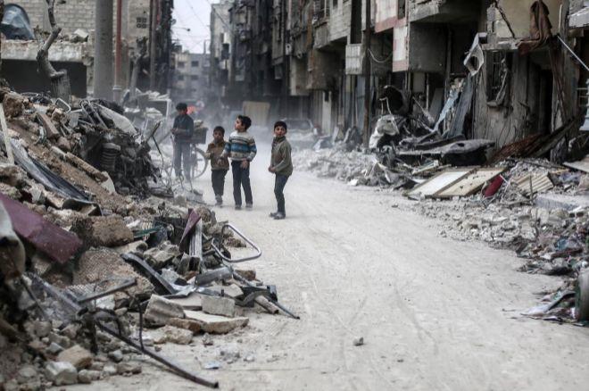 Varios niños buscan sus pertenencias entre los escombros de los edificios tras un bombardeo en Duma.