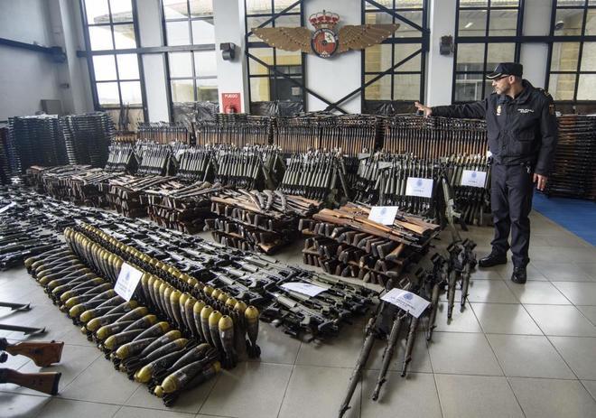 Agente de la Policía Nacional muestra las armas incautadas.