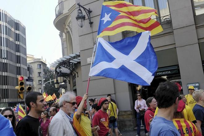 Un joven sostiene una 'estelada' y una bandera escocesa en una...