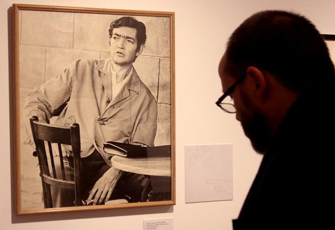 Un visitantes delante de un retrato de Julio Cortázar, en la exposición de la Fundación Cajasol.