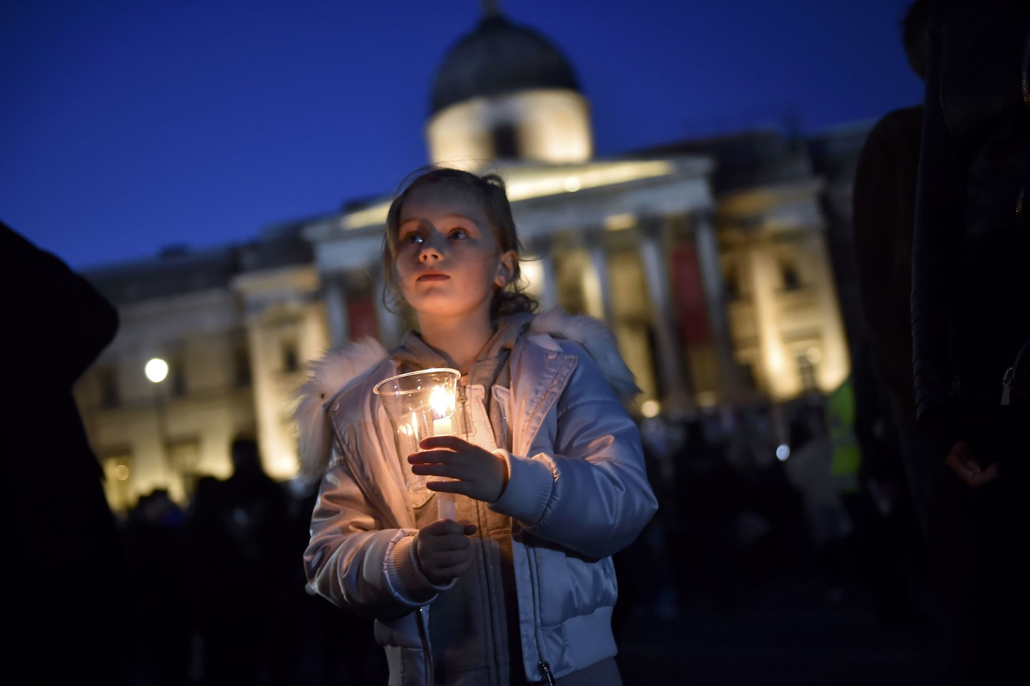 La gente enciende velas en la vigilia en Trafalgar Square al día...