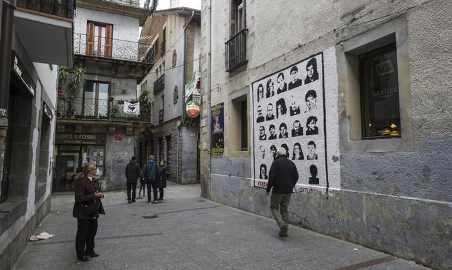 Un hombre delante de un mural en Hernani (Guipúzcoa) con rostros de...