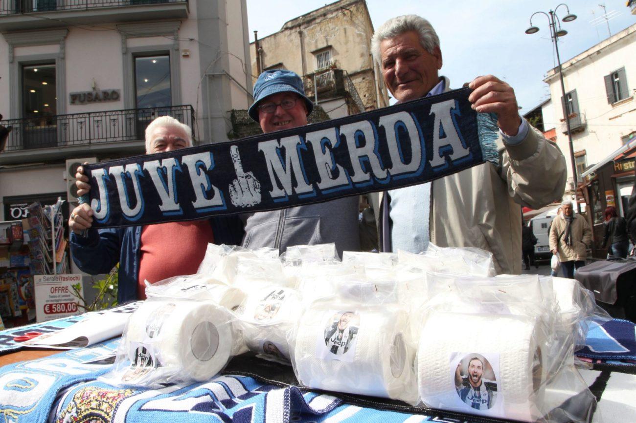 Vendedores posan con una bufanda de Juve Merda.
