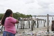 Una mujer contempla las ruinas de una casa en un pueblo pesquero de Esmeraldas.