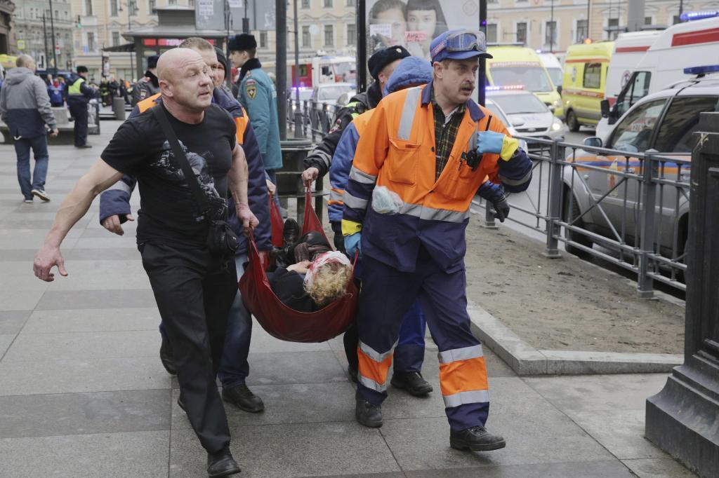 Bomberos transportan a una mujer, víctima del atentado en San Petersburgo.