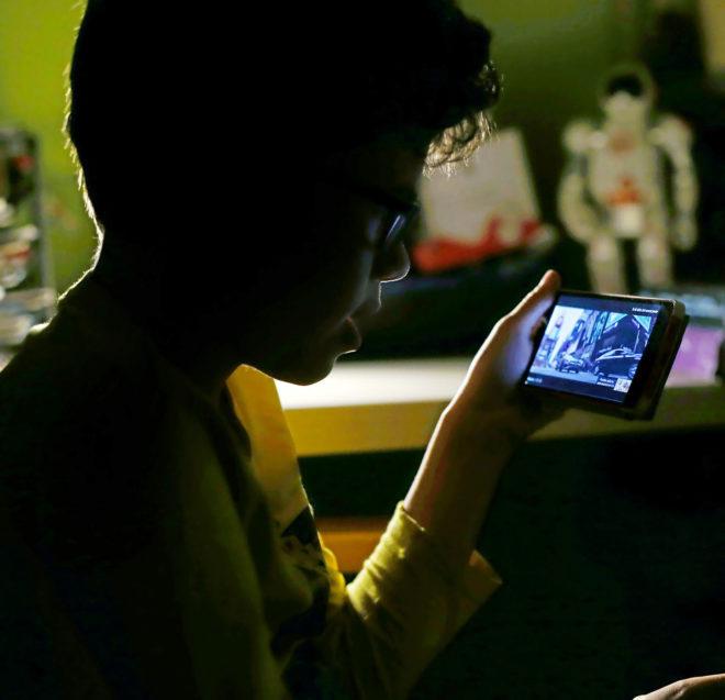 Un niño ante la pantalla de un teléfono móvil.