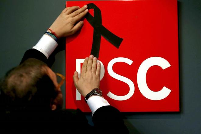 Un militante coloca un crespón negro en la sede del PSC en Barcelona en recuerdo de Carme Chacón.