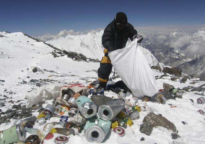 Un sherpa recoge basura durante una expedición al Monte Everest.
