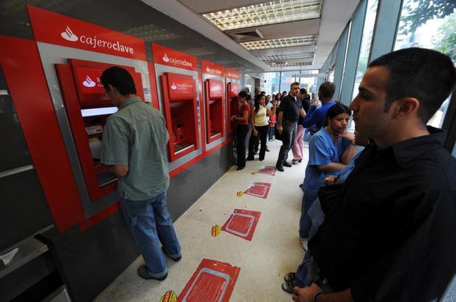 Personas sacando dinero en una sucursal del Banco Santander.