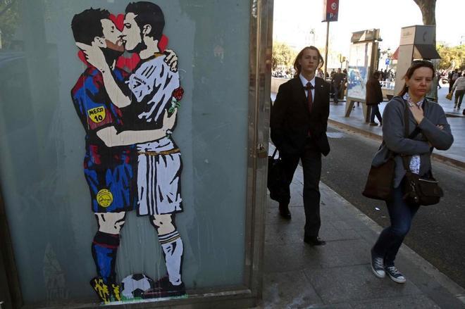 Grafiti en el centro de Barcelona con el beso entre Leo Messi y  Cristiano Ronaldo