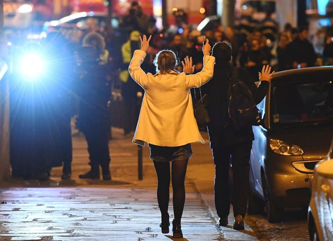 Viandantes levantan los brazos mientras caminan hacia agentes de policía.