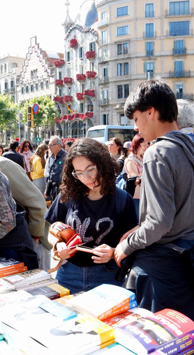 Lectores a la búsqueda del libro ideal en una parada de paseo de Gràcia, con la Casa Batlló engalanada de rosas de fondo.