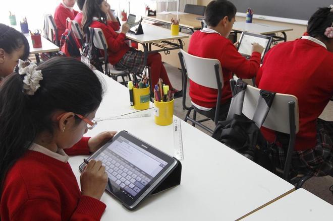 Un grupo de niños estudia en el aula con tabletas.