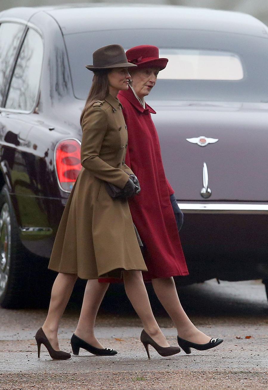 Con abrigo de corte militar y sombrero, para asistir al oficio...