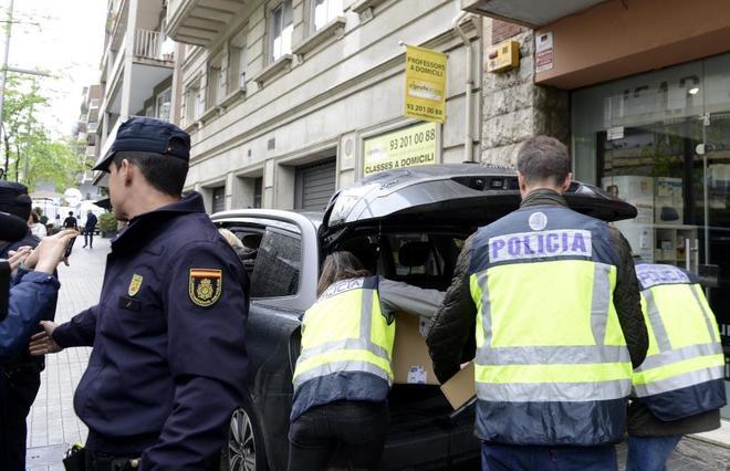 Agentes de la Policía trasladan cajas tras el registro a la vivienda...
